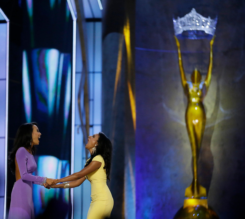 Description of . Miss New York Nina Davuluri, right, reacts with Miss California Crystal Lee after Davuluri won Miss America 2014 pageant, Sunday, Sept. 15, 2013, in Atlantic City, N.J. (AP Photo/Julio Cortez)