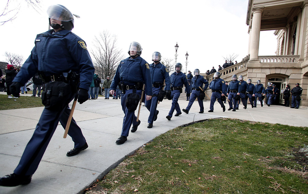 Description of . Michigan State Police leave a staging area to walk through the crowd of union members who gathered from around the country to rally at the Michigan State Capitol to protest a vote on Right-to-Work legislation December 11, 2012 in Lansing, Michigan. Republicans control the Michigan House of Representatives, and Michigan Gov. Rick Snyder has said he will sign the bill if it is passed. The new law would make requiring financial support of a union as a condition of employment illegal. (Photo by Bill Pugliano/Getty Images)