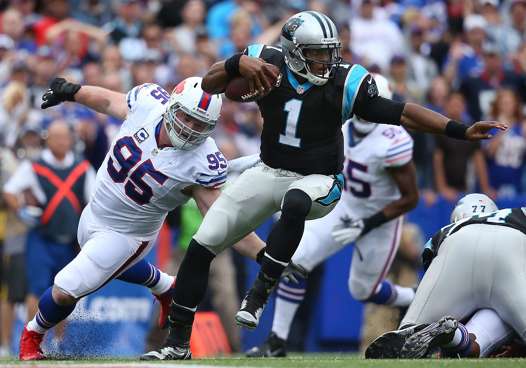 Description of . Cam Newton #1 of the Carolina Panthers escapes pressure during NFL game action from Kyle Williams #95 of the Buffalo Bills at Ralph Wilson Stadium on September 15, 2013 in Orchard Park, New York. (Photo by Tom Szczerbowski/Getty Images)