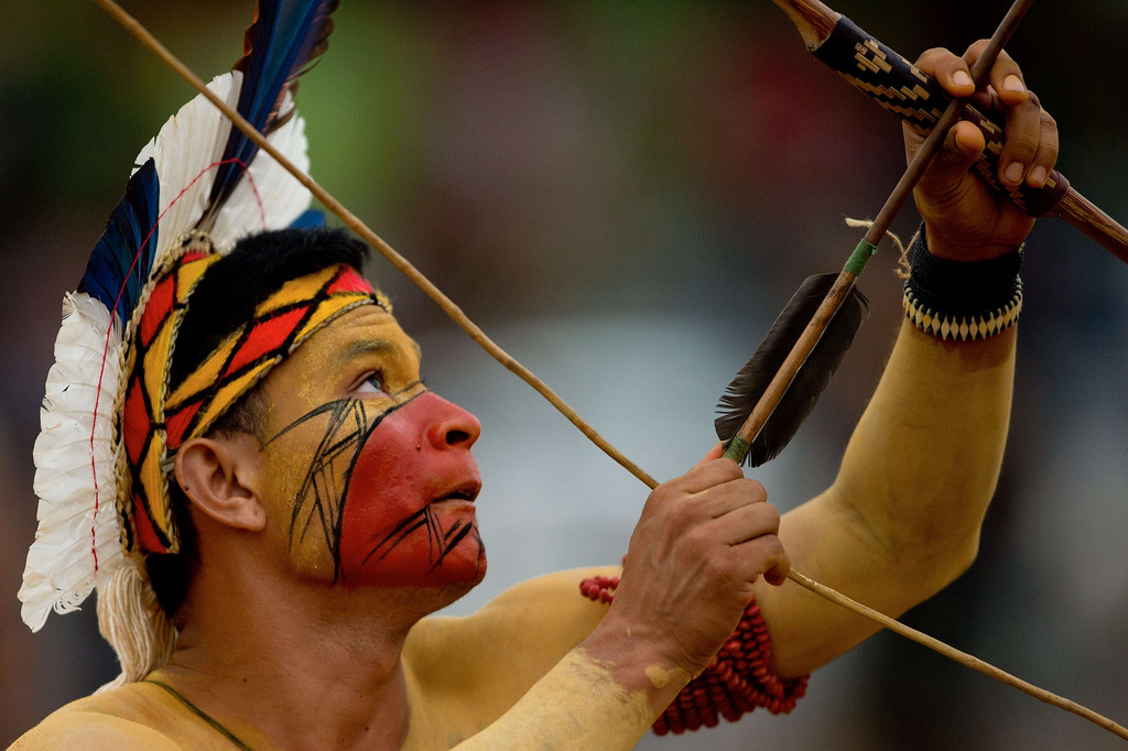 Description of . A Brazilian indigenous man of the Pataxo tribe takes part in the bow and arrow competition during the XII International Games of Indigenous Peoples in Cuiaba, Mato Grosso state, Brazil on November 12, 2013. 1500 natives from 49 Brazilian ethnic groups and from another 17 countries are gathering in Cuiaba until November 16 to compete in some 30 athletic disciplines, many of their own. AFP PHOTO / Christophe  SIMON/AFP/Getty Images