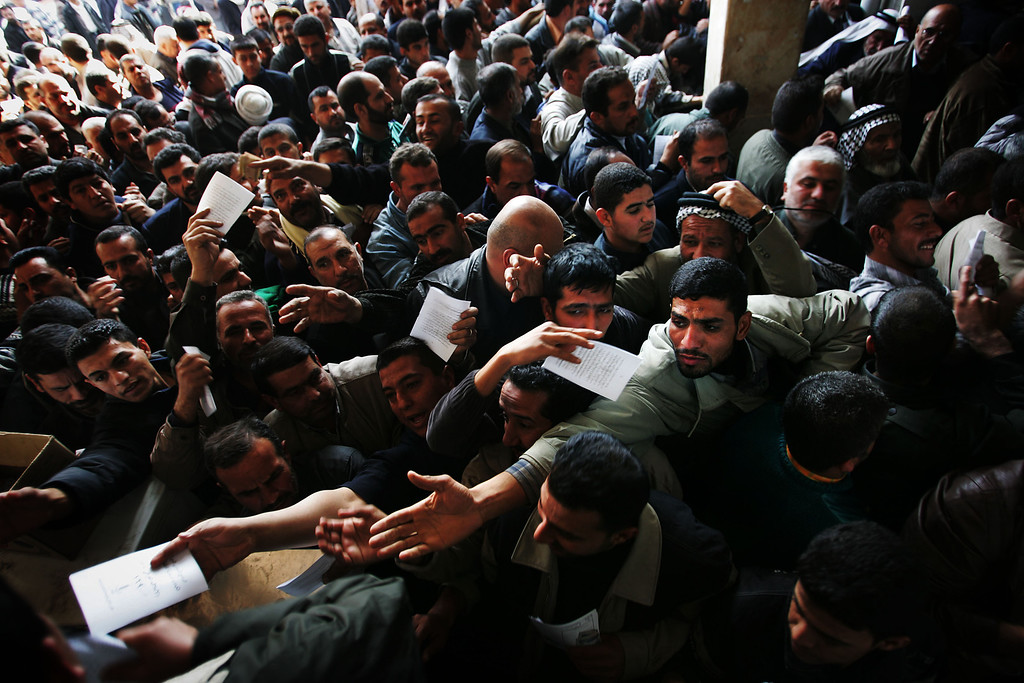 Description of . Shia Iraqi men crush in to get election pamphlets from the United Iraqi Alliance, a coalition of various Shia political and religious parties, as they are handed out Buratha Mosque December 31, 2004, in Baghdad, Iraq. (Photo by Chris Hondros/Getty Images)
