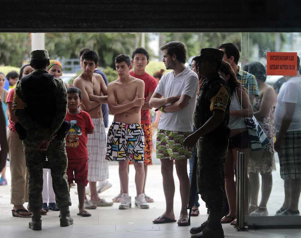 Description of . Residents and tourists queue to buy supplies outside a supermarket guarded by soldiers in Acapulco, state of Guerrero, Mexico, after heavy rains hit the area on September 17, 2013. Mexican officials launched an airlift to evacuate tens of thousands of tourists stranded in the flooded resort of Acapulco on Tuesday following a pair of deadly major storms. The official death toll rose to 47 after the tropical storms, Ingrid and Manuel, swarmed large swaths of the country during a three-day holiday weekend, sparking landslides and causing rivers to overflow in several states.  Pedro PARDO/AFP/Getty Images