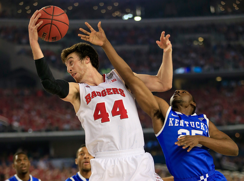 Description of . ARLINGTON, TX - APRIL 05: Frank Kaminsky #44 of the Wisconsin Badgers grabs a rebound over Dominique Hawkins #25 of the Kentucky Wildcats  during the NCAA Men's Final Four Semifinal at AT&T Stadium on April 5, 2014 in Arlington, Texas.  (Photo by Jamie Squire/Getty Images)