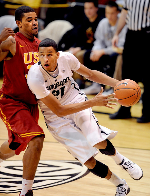 Description of . Andre Roberson of Colorado drives around Eric Wise of USC during the second half of the January 10, 2013 game in Boulder.   Cliff Grassmick/Daily Camera