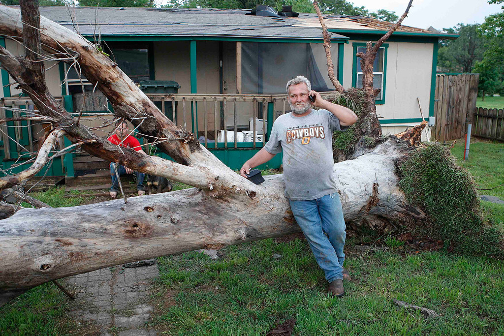 Description of . Allen Cook talks on his cell phone as he stands next to a downed tree which missed falling on a home in a mobile home park, where several other homes were destroyed by a tornado on Sunday, west of Shawnee, Oklahoma May 19, 2013. A tornado half a mile wide struck near Oklahoma City on Sunday, part of a massive storm front that hammered the central United States. News reports said at least one person had died. REUTERS/Bill Waugh