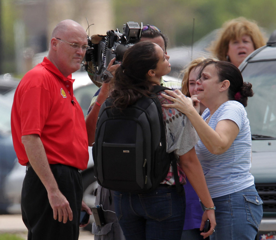 Description of . Lone Star College student Michelle Alvarez, second from right, is examined by her aunt Elena Tokarew, right,  after the stabbings at Lone Star College's Cypress-Fairbanks campus Tuesday April 9, 2013, in Cyprus, Texas.  Alvarez was one of the injured in the stabbing attack at the campus.    (AP Photo/Houston Chronicle, James Nielsen)