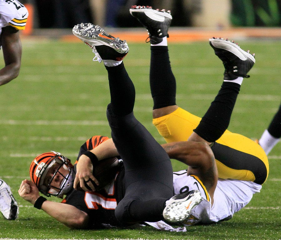 Description of . Cincinnati Bengals quarterback Andy Dalton, left, is tackled after a short gain by Pittsburgh Steelers outside linebacker LaMarr Woodley in the second half of an NFL football game, Monday, Sept. 16, 2013, in Cincinnati. (AP Photo/Tom Uhlman)