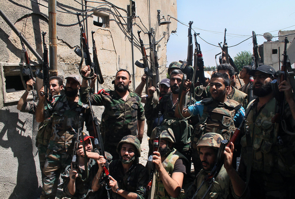 Description of . In this Sunday, July 14, 2013 file photo, Syrian soldiers cheer after battling with rebels during a tour for journalists organized by the Syrian Information Ministry in the Damascus suburb of Jobar, Syria. More than two years into Syria's civil war, the once highly-centralized authoritarian state has effectively split into three distinct parts, each boasting its own flags, security agencies and judicial system. (AP Photo/Bassem Tellawi)