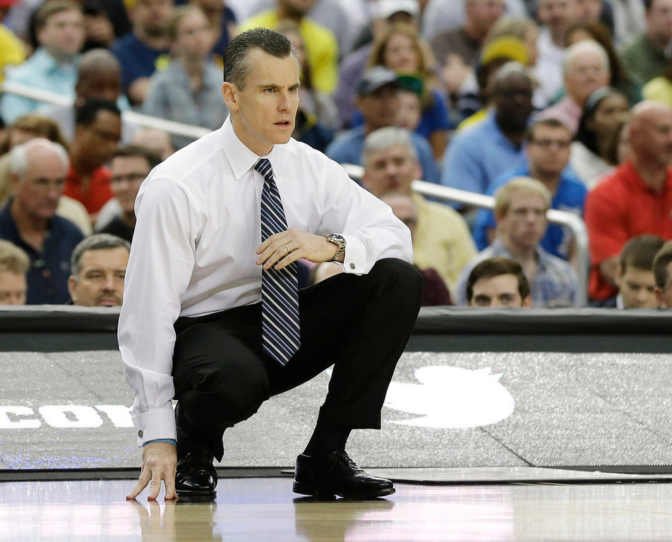 Description of . Florida head coach Billy Donovan watches action against Michigan during the first half of a regional final game in the NCAA college basketball tournament, Sunday, March 31, 2013, in Arlington, Texas.  (AP Photo/Tony Gutierrez)