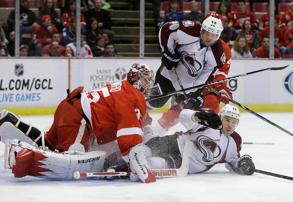 Description of . Colorado Avalanche right wing Chuck Kobasew (12) slides into Detroit Red Wings goalie Jimmy Howard (35) during the first period of an NHL hockey game in Detroit, Tuesday, March 5, 2013. (AP Photo/Carlos Osorio)