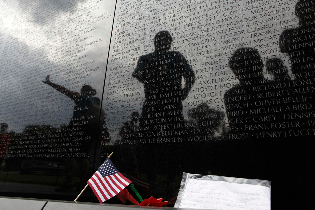 . Visitors are reflected at the Vietnam Veterans Memorial wall, etched with the names of more than 58,000 U.S. servicemen and women who died in the war, before the Memorial Day weekend in Washington May 23, 2013. REUTERS/Yuri Gripas