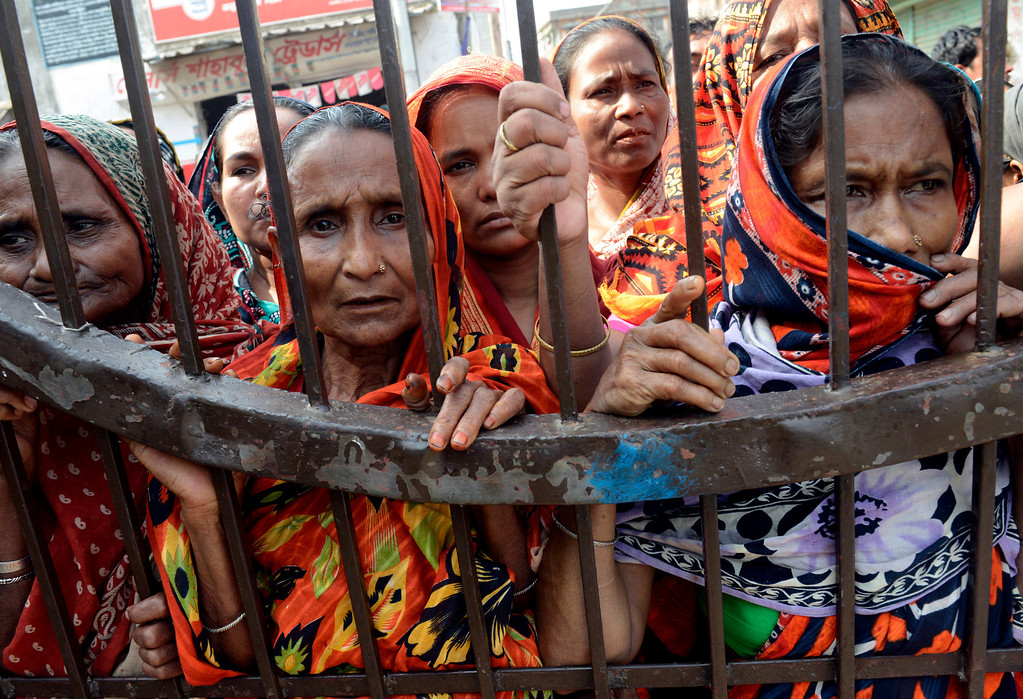 Description of . Women watch from behind a gate while unclaimed bodies are brought to a cemetery from the garment factory building collapse in preparation for a mass burial on Wednesday May 1, 2013 in Dhaka, Bangladesh. (AP Photo/Ismail Ferdous)