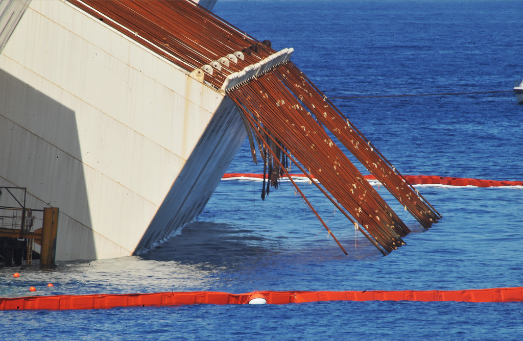 Description of . Caissons attached to the side of the stricken Costa Concordia and the cabling used to pull the ship upright are seen as the parbuckling project to raise the ship continues on September 16, 2013 in Isola del Giglio, Italy. Work begins today to right the stricken Costa Concordia vessel, which sank on January 12, 2012. If the operation is successful, it will then be towed away and scrapped. The procedure, known as parbuckling, has never been carried out on a vessel as large as Costa Concordia before. (Photo by Laura Lezza/Getty Images)