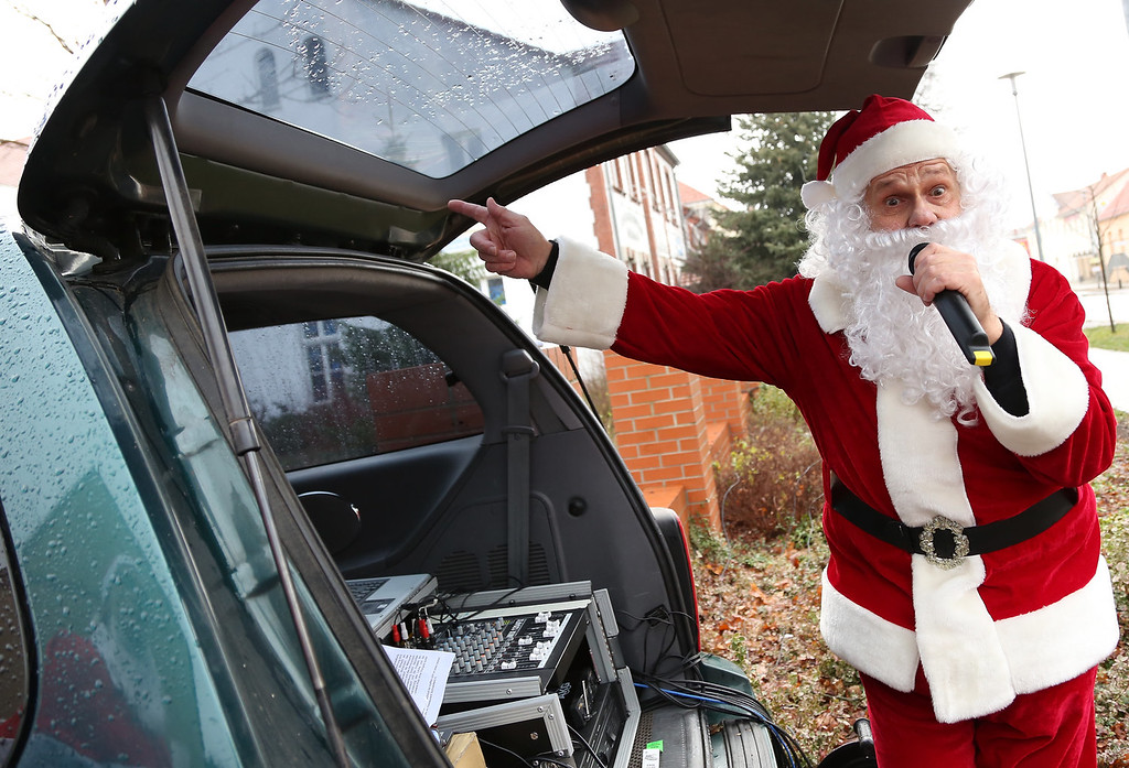 Description of . An announcer dressed as Santa Claus emcess from the back of a car during the 5th annual Michendorf Santa Run (Michendorfer Nikolauslauf) on December 8, 2013 in Michendorf, Germany. Over 900 people took part in this year's races, which included one for children and one for adults.  (Photo by Adam Berry/Getty Images)