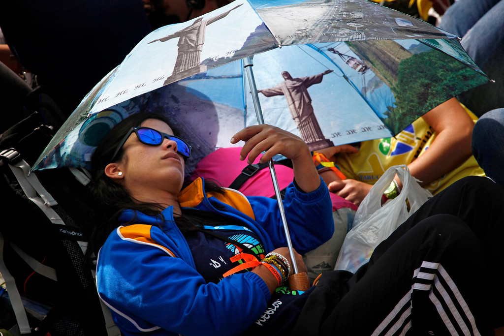 Description of . A pilgrim rests under an umbrella decorated with images of the Christ the Redeemer statue as she waits on Copacabana beach for an evening vigil with Pope Francis during World Youth Day events in Rio de Janeiro, Brazil, Saturday, July 27, 2013. Francis will preside over an evening vigil service on Copacabana beach that is expected to draw more than 1 million young people. (AP Photo/Jorge Saenz)