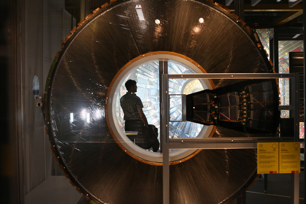 Description of . A visitor to the Science Museum is seen through a cross section of a Transition Radiation Tracker Wheel prototype, part of the Large Hadron Collider (LHC) at the 'Collider' exhibition on November 12, 2013 in London, England.  (Photo by Peter Macdiarmid/Getty Images)