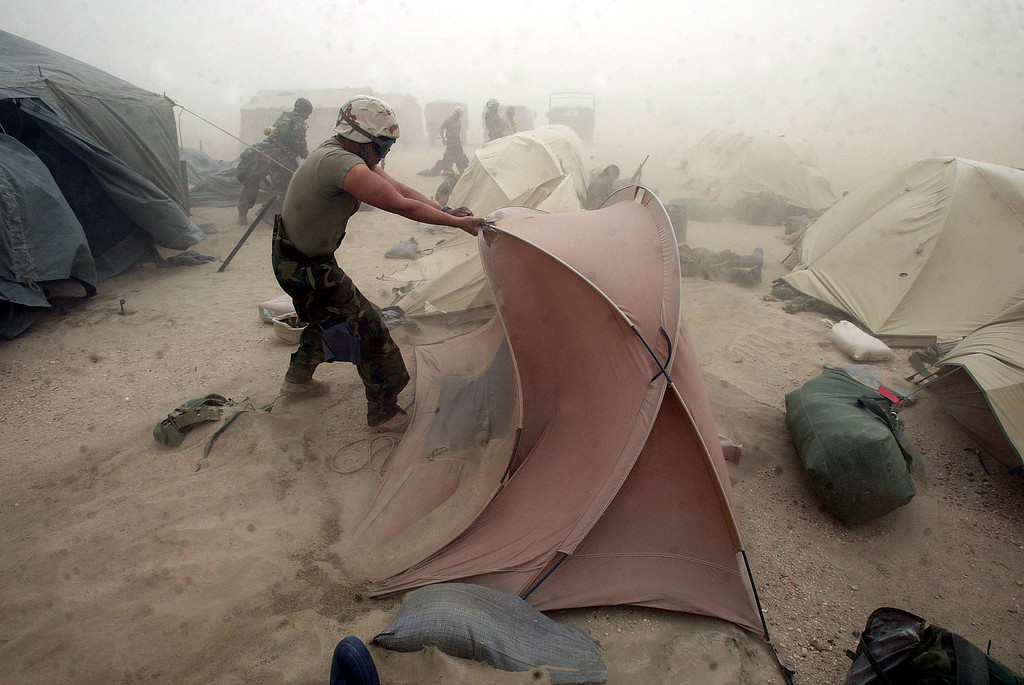 . Marine Corp. Eric Silva, of New Jersey, fights the wind for his tent during a severe sandstorm at Camp Viper in the Iraqi desert, Tuesday, March 25, 2003. The storm brought dust and sand from as far away as Egypt and Libya. (AP Photo/San Francisco Chronicle, Michael Macor)