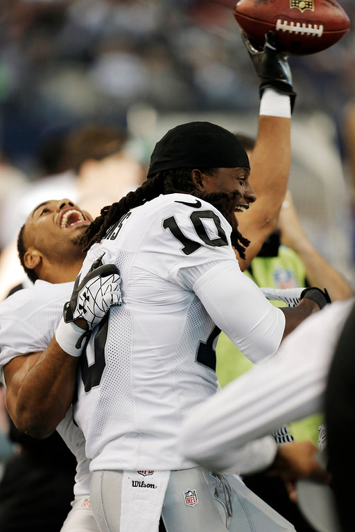Description of . Oakland Raiders wide receiver Greg Jenkins (10) celebrates his touchdown against the Dallas Cowboys with Rashad Jennings (27) during the first half of an NFL football game, Thursday, Nov. 28, 2013, in Arlington, Texas.  (AP Photo/Brandon Wade)