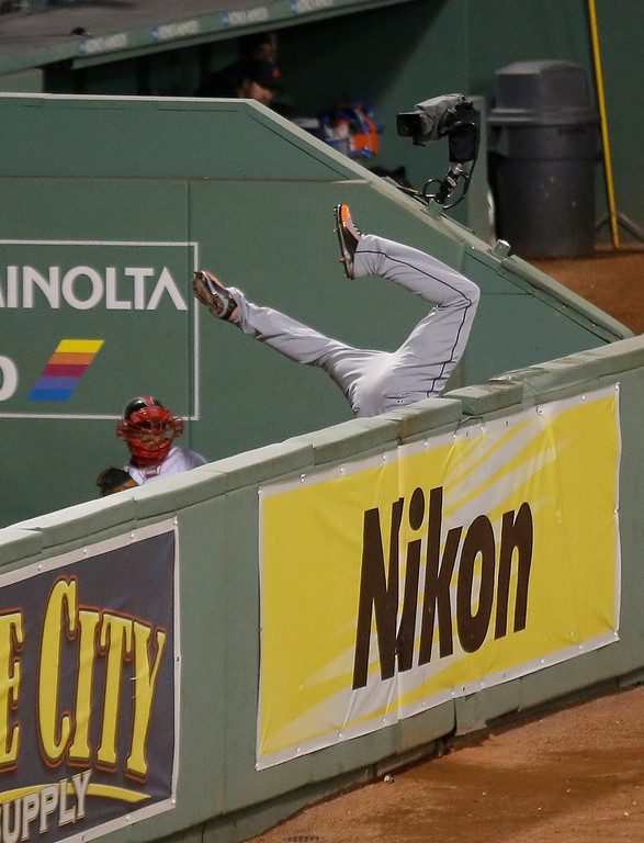 Description of . Detroit Tigers' Torii Hunter leaps and misses a catch as Boston Red Sox's David Ortiz hits a grand slam home run in the eighth inning during Game 2 of the American League baseball championship series Sunday, Oct. 13, 2013, in Boston. (AP Photo/Charlie Riedel)