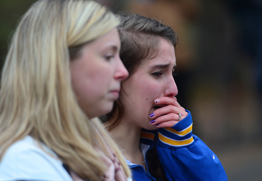 Description of . Two teenagers grieve while paying their respects at a makeshift shrine to the victims of a elementary school shooting in Newtown, Connecticut, December 16, 2012.  A young gunman slaughtered 20 small children and six teachers on December 14,2012 after walking into a school in an idyllic Connecticut town wielding at least two sophisticated firearms.  EMMANUEL DUNAND/AFP/Getty Images