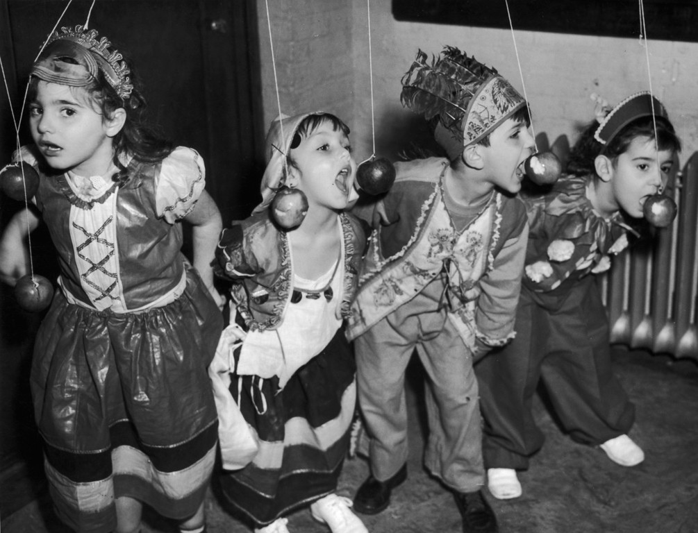 Description of . circa 1940:  From left to right, Elizabeth Bianco, Barbara Lee, Anthony Dimino and Theresa Imbronone join in the fun at a Halloween party in New York City. The party was organised for members of Tots' Town, a day care facility at the Children's Aid Society's James Center.  (Photo by Keystone/Getty Images)