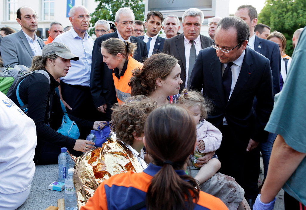 Description of . French President Francois Hollande comforts victims during a visit on the site of an intercity train accident at the Bretigny-sur-Orge train station near Paris July 12, 2013. REUTERS/Kenzo Tribouillard/Pool