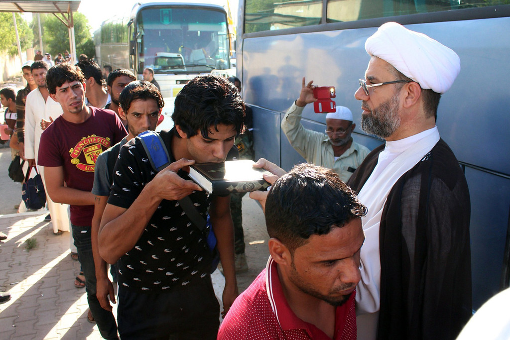 Description of . An Iraqi civilian, volunteering to fight a militant offensive, kisses a Koran book as he queues with comrades before boarding buses to reach Mosul on June 15, 2014, in the southern port city of Basra. Leading Shiite cleric Grand Ayatollah Ali al-Sistani urged Iraqis on June 13 to take up arms against Sunni militants marching on Baghdad, as thousands volunteered to bolster the capital's defences. AFP PHOTO/ STR-/AFP/Getty Images