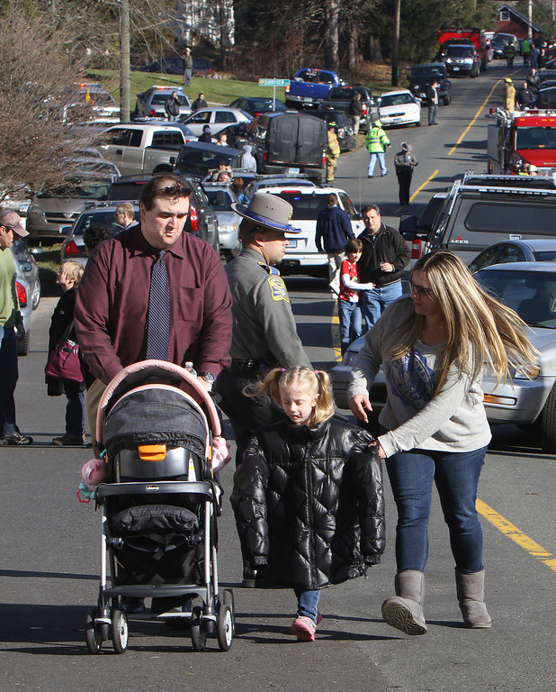 Description of . Parents walk away from the Sandy Hook School with their children following a shooting at the school Friday, Dec. 14, 2012 in Newtown, Conn. A man opened fire inside the Connecticut elementary school where his mother worked Friday, killing 26 people, including 18 children, and forcing students to cower in classrooms and then flee with the help of teachers and police. (AP Photo/The Journal News, Frank Becerra Jr.)