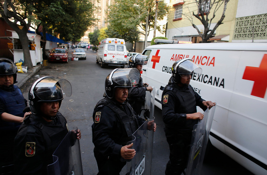 Description of . Ambulances pass a police line near the headquarters of state oil giant Pemex in Mexico City January 31, 2013. An explosion rocked Pemex on Thursday, killing at least 14 people and injuring 80 others, the government said. The blast, which media reports said was caused by machinery, hit the lower floors of the downtown building, throwing debris into the streets and sending workers running outside.  REUTERS/Tomas Bravo
