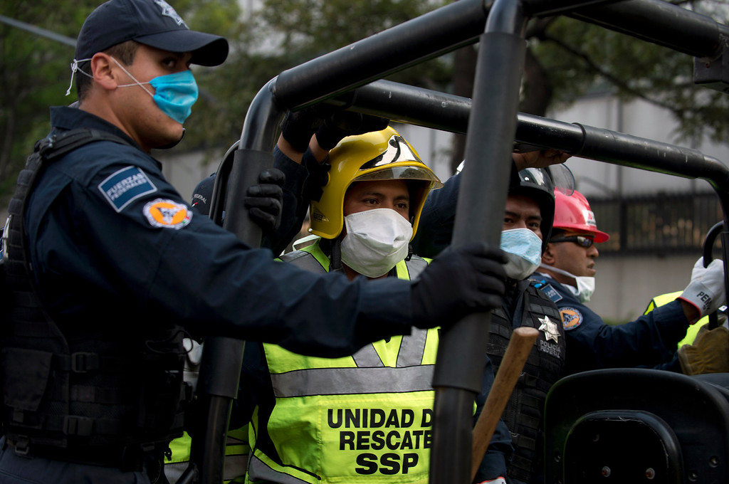 Description of . Rescuers are driven inside the premises of the skyscraper that houses the headquarters of state-owned Mexican oil giant Pemex, following a blast inside the building in Mexico City on January 31, 2013.   YURI CORTEZ/AFP/Getty Images