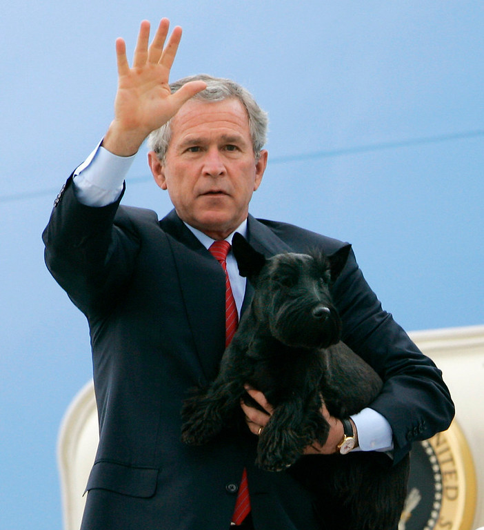 Description of . President Bush steps down from Air Force One, holding his dog Barney, at Andews Air Force Base, Md., as he arrives from a visit with soldiers at Ft. Hood, Texas, Tuesday, April 12, 2005. Bush left Washington for Rome on Wednesday and after the pope's funeral flew directly to Texas for a weekend at his ranch where he met with Israeli Prime Minister Ariel Sharon  Monday.  (AP Photo/J. Scott Applewhite)