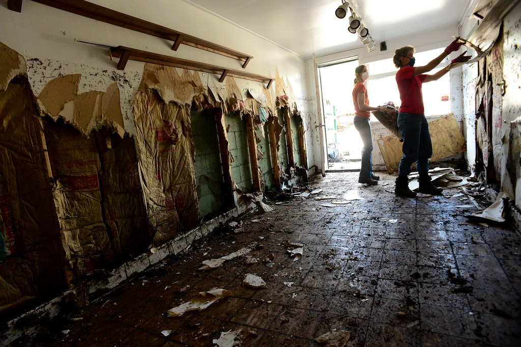 Description of . GLEN HAVEN, CO - OCTOBER 8: Volunteers Katherine Dumont, middle, and Barb Trofholz help take flood damaged dry wall off of the walls of Tuck N' Tresures gift shop next to the historic Glen Haven Inn in Glen Haven, CO on October 8, 2013.  The Inn was one of the only businesses that actually made it in the town but has been inundated with mud and debris.  The water line along the walls suggest that the flood waters reached at least four feet inside the building.  Owners Sheila and Tom Sellers have owned the Inn for over 20 years and have spent that same amount of time lovingly collecting antiques to create the victorian inspired interior of the Inn and restaurant. (Photo By Helen H. Richardson/ The Denver Post)