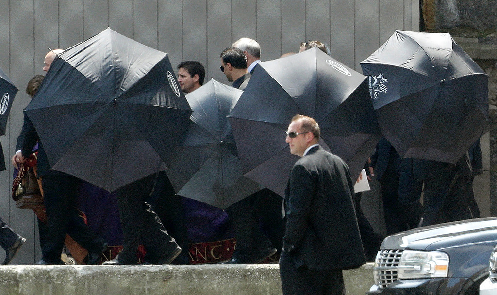 Description of . Men hold umbrellas as pallbearers walk with a casket containing the body of actor James Gandolfini at Cathedral Church of Saint John the Divine after funeral services for Gandolfini, Thursday, June 27, 2013, in New York. (AP Photo/Julio Cortez)