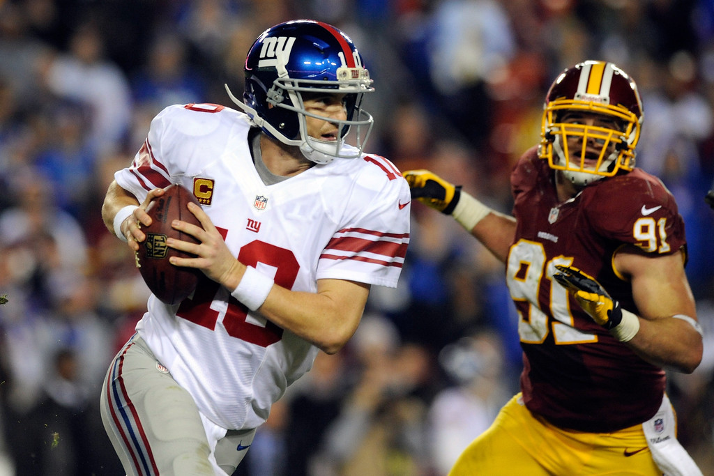 Description of . LANDOVER, MD - DECEMBER 03:  Quarterback Eli Manning #10 of the New York Giants scrambles as he is being chased by Ryan Kerrigan #91 of the Washington Redskins in the third quarter against the Washington Redskins at FedExField on December 3, 2012 in Landover, Maryland.  (Photo by Patrick McDermott/Getty Images)