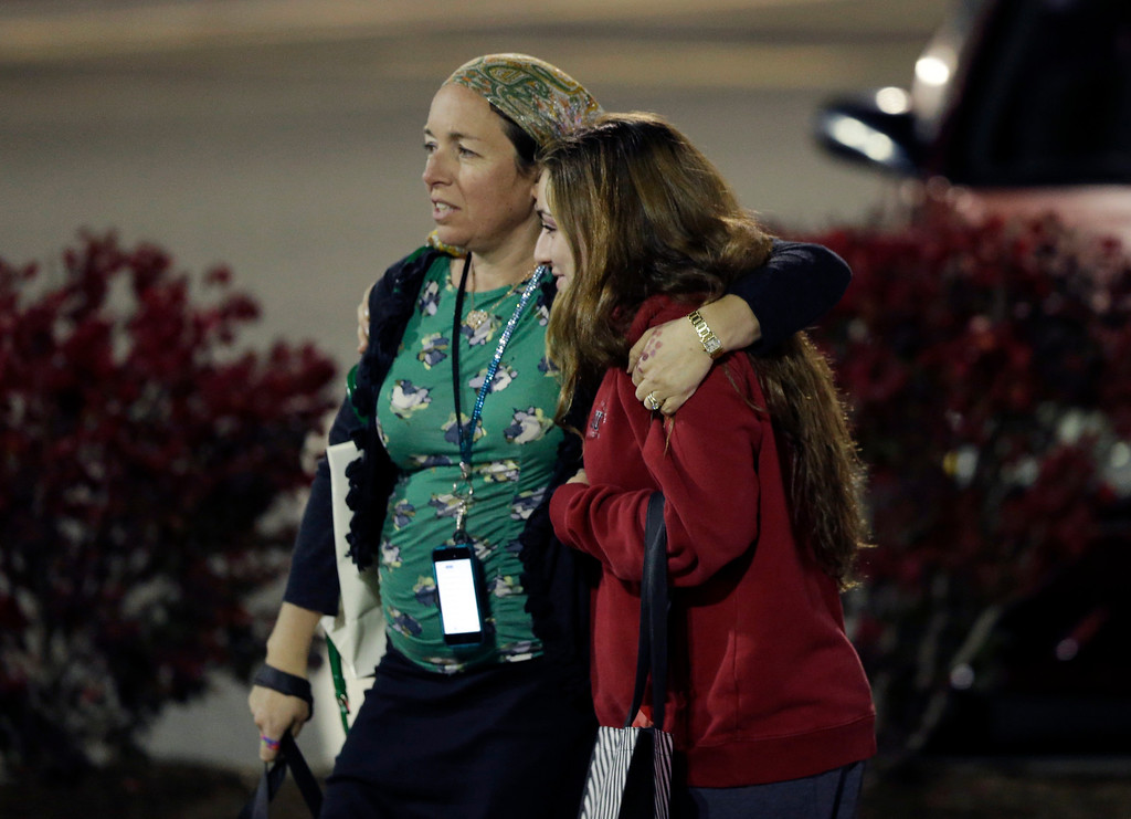 Description of . Two women walk in the parking lot of the Garden State Plaza Mall with officials standing guard following reports of a shooter, Monday, Nov. 4, 2013, in Paramus, N.J. Hundreds of law enforcement officers converged on the mall Monday night after witnesses said multiple shots were fired there. (AP Photo/Julio Cortez)