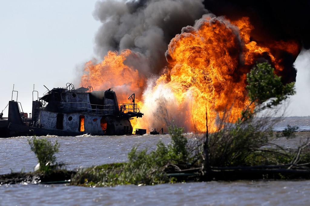 Description of . A fire still burns after a tugboat and barge hit a gas pipeline yesterday evening in Perot Bay in Lafourche Parish, La., Wednesday, March 13, 2013. (AP Photo/Gerald Herbert)