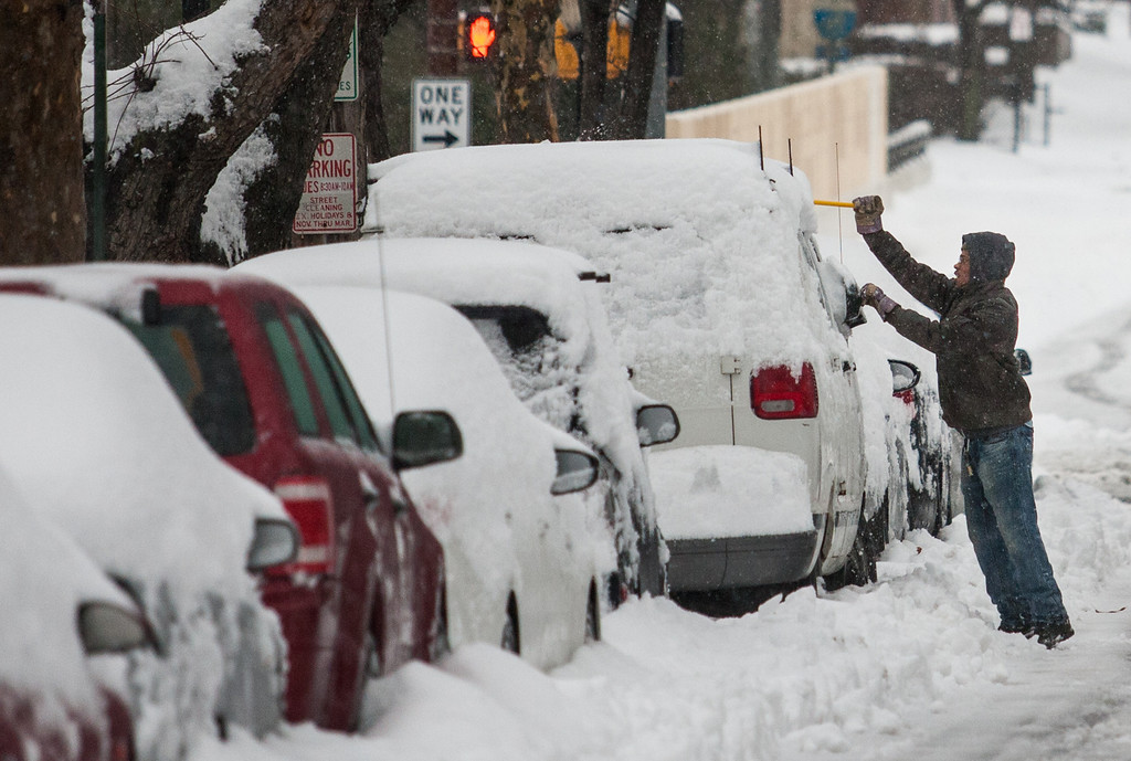 Description of . A man clears off his car on 10th street, in downtown Wilmington, Del. on Thursday morning, Feb. 13, 2014. The city saw nearly a foot of snow fall over night, and residents were forced to dig out in blowing sleet in the morning. (AP Photo/The News Journal, Kyle Grantham)