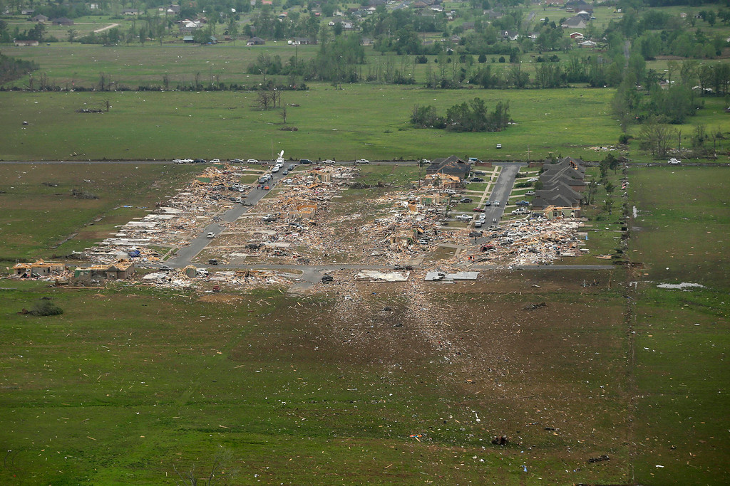 Description of . A debris trail, bottom, left when a tornado struck a Vilonia, Ark., neighborhood, leads from the rows of houses Monday, April 28, 2014, after a tornado struck the town late Sunday, killing at least 16 people.   (AP Photo/Danny Johnston)