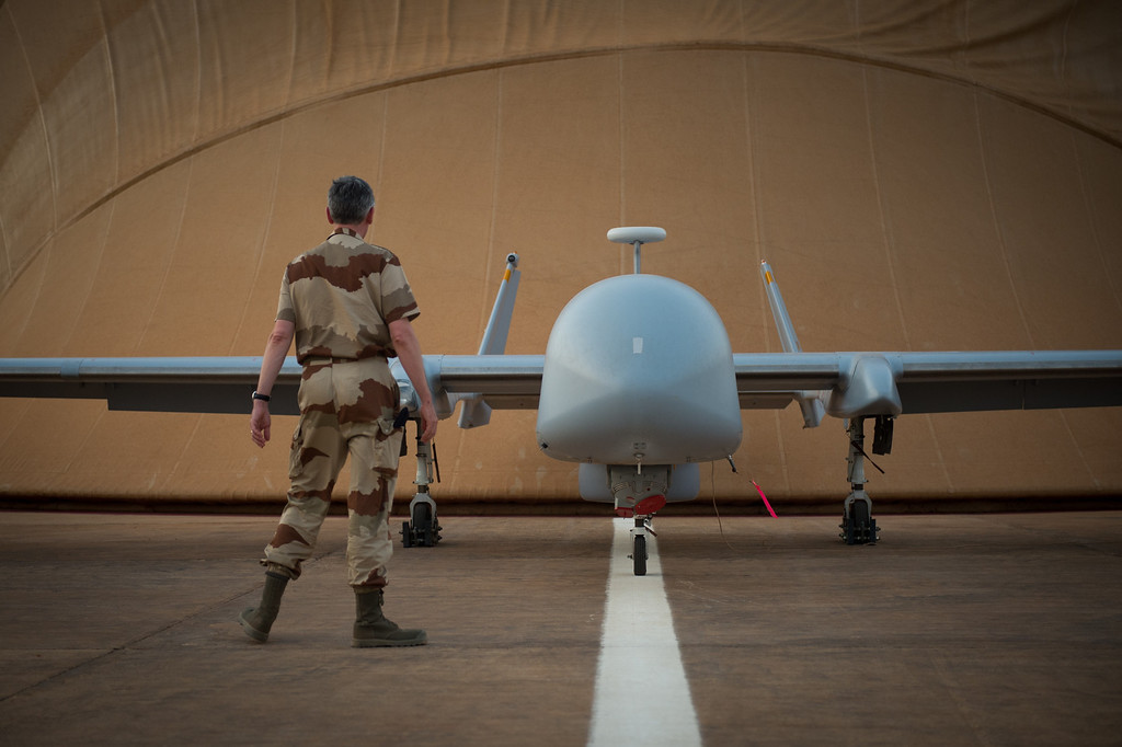 Description of . A French soldier of the Serval operation in Mali stands in front of a Harfang drone on April 26, 2013 on the French army base of Niamey. MARTIN BUREAU/AFP/Getty Images