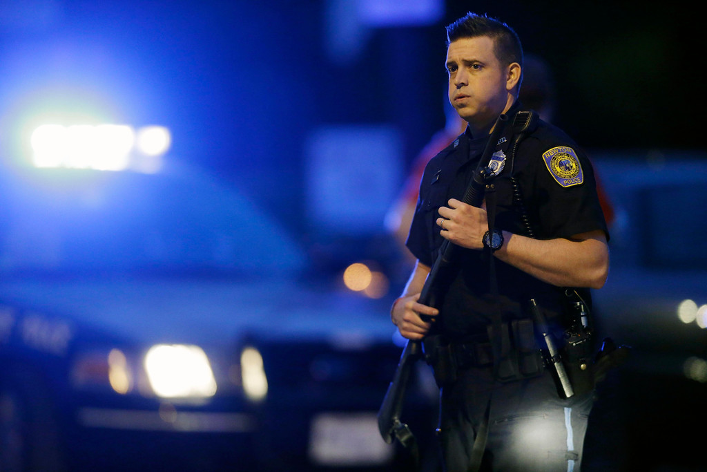 Description of . A police officer stands guard at the scene as the search for suspect in the Boston Marathon bombings continues , Friday, April 19, 2013, in Watertown, Mass. Gunfire erupted Friday night amid the manhunt for the surviving suspect in the Boston Marathon bombing, and police in armored vehicles and tactical gear rushed into the Watertown neighborhood in a possible break in the case.  (AP Photo/Matt Rourke)