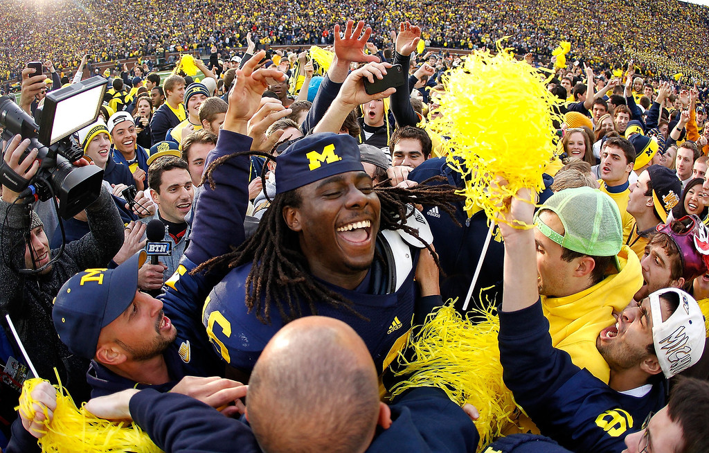 Description of . Denard Robinson #16 of the Michigan Wolverines celebrates with students after beating Ohio State 40-34 at Michigan Stadium on November 26, 2011 in Ann Arbor, Michigan. (Photo by Gregory Shamus/Getty Images)