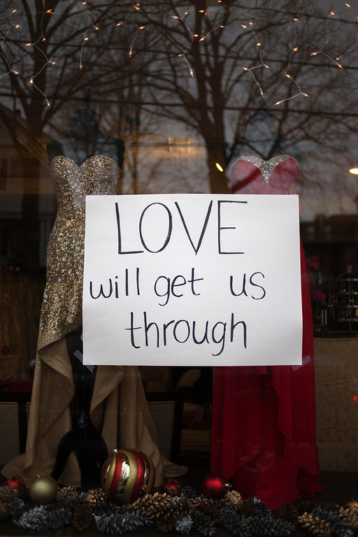 Description of . A sign for victims of the Sandy Hook Elementary shooting hangs in the window of a women's dress shop in Newtown, Connecticut December 16, 2012. Worshippers filled Sunday services to mourn the victims of a gunman's elementary school rampage that killed 20 children and six adults with President Barack Obama due to appear later at an interfaith vigil to help this shattered Connecticut town recover.   REUTERS/Adrees Latif