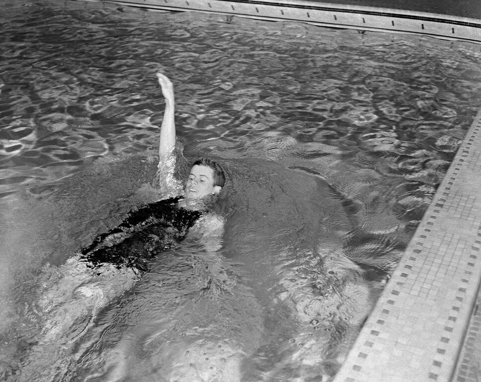 Description of . Kennedy swims in the backstroke event for the varsity swimming team at Harvard on March 10, 1938.  Associated Press file