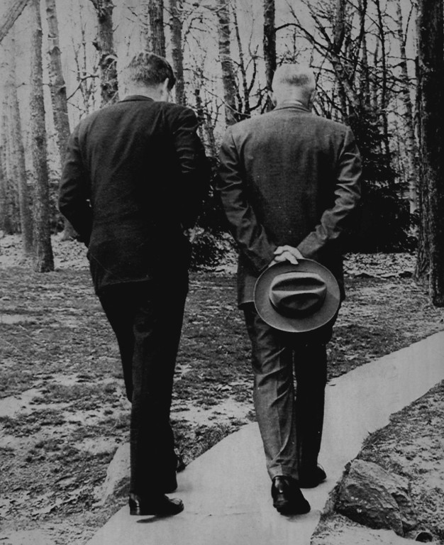 Description of . Kennedy and former President Eisenhower walk a  path at Camp David in this picture, symbolic of the change from the '50s to the '60s in January 1961. Denver Post file