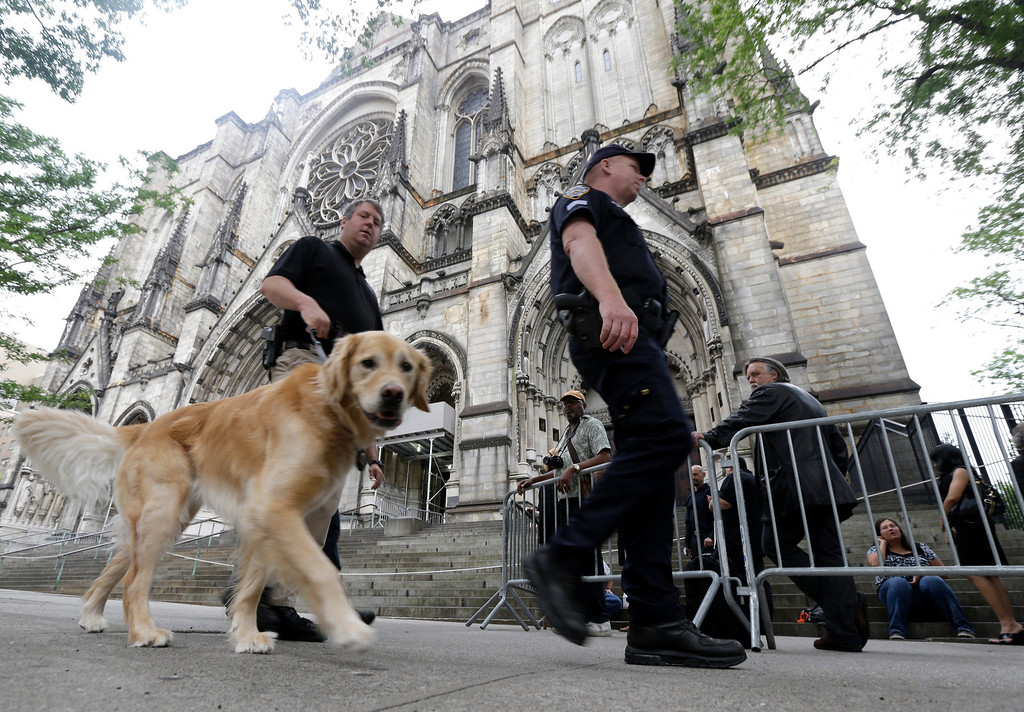 Description of . Officials walk with a dog as they secure an area outside of at Cathedral Church of Saint John the Divine, where people gathered behind a barricade, before funeral services for actor James Gandolfini, Thursday, June 27, 2013, in New York. (AP Photo/Julio Cortez)