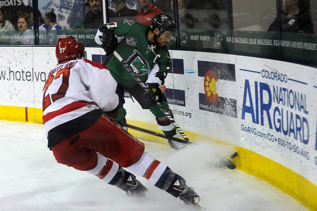 Description of . DENVER, CO - MAY 2: Aaron MacKenzie (37) of the Denver Cutthroats clears the puck off the boards as Darryl Bootland (27) of the Allen Americans attempts to block the pass during the third period of game 1 of the Ray Miron Presidents Cup Finals at the Denver Coliseum in Denver, Colorado on May 2, 2014. (Photo by Seth McConnell/The Denver Post)