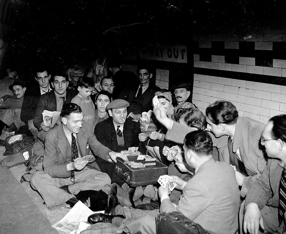 Description of . Londoners sheltering in a London Underground station from the Nazi bombing raids, play cards through the night to pass the time, Sept. 25, 1940. (AP Photo)