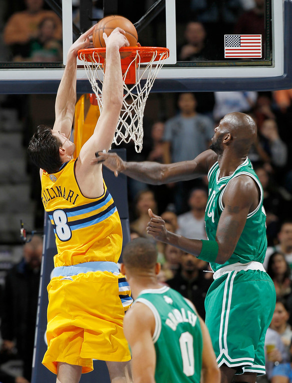 Description of . Denver Nuggets forward Danilo Gallinari, of Italy, drops the ball in for a basket as Boston Celtics forward Kevin Garnet, right, and guard Avery Bradley watch during the first quarter of an NBA basketball game in Denver on Tuesday, Feb. 19, 2013. (AP Photo/David Zalubowski)