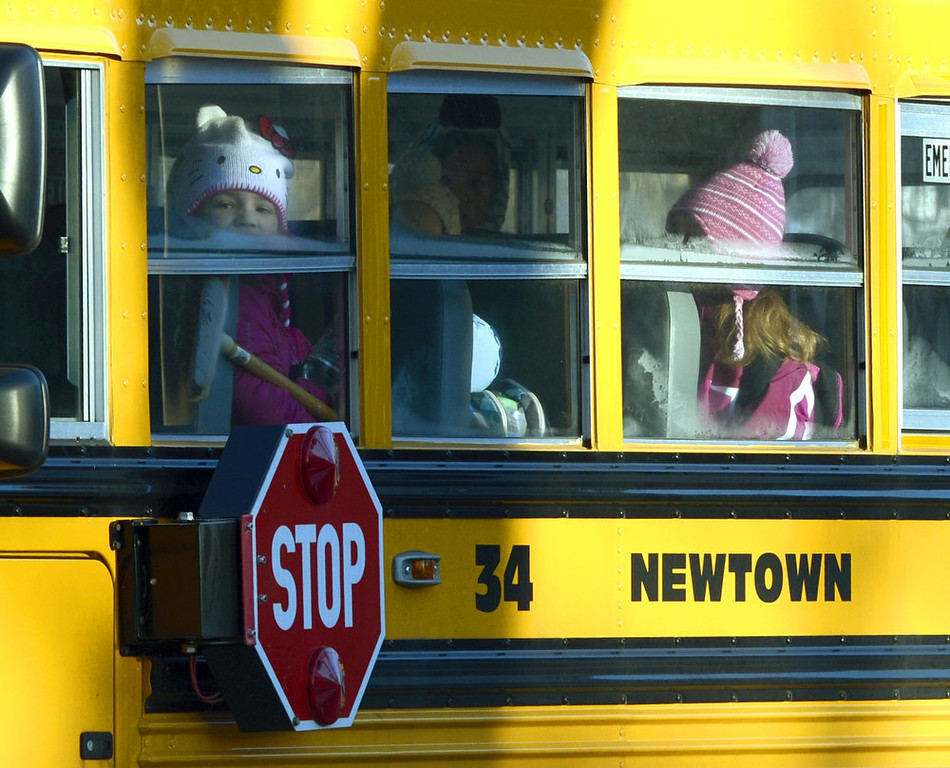 Description of . A Sandy Hook Elementary student looks out the window as children leave on a school bus in Newtown, Connecticut on January 3, 2013.  Students at the elementary school where a gunman massacred 26 children and teachers last month were returning Thursday to classes at an alternative campus described by police as