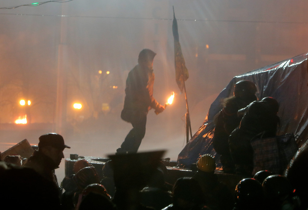 Description of . An anti-government protester, center, prepares to throw a Molotov cocktail during clashes with riot police in Kiev's Independence Square, the epicenter of the country's current unrest,  Kiev, Ukraine, Tuesday, Feb. 18, 2014.  (AP Photo/Efrem Lukatsky)